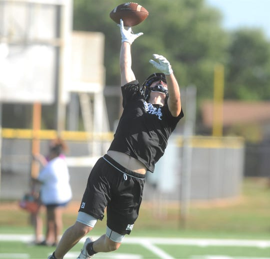 Abilene High wide receiver Luke Tebow tries to haul in a high pass Monday, Aug. 12, 2019, during the first fall football practice of the season on the on-campus turf practice field.