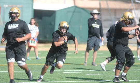 Abilene High running back Esai Jaques hits the hole Monday, Aug. 12, 2019, during the first fall football practice of the season on the on-campus turf practice field.