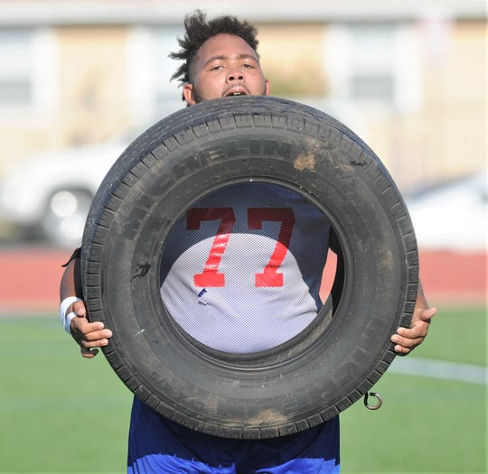 Cooper offensive lineman Devon Cosby carries a tire during a conditioning drill on the Cougars' first day of fall practice Monday, Aug. 12, 2019, at Cooper High School.