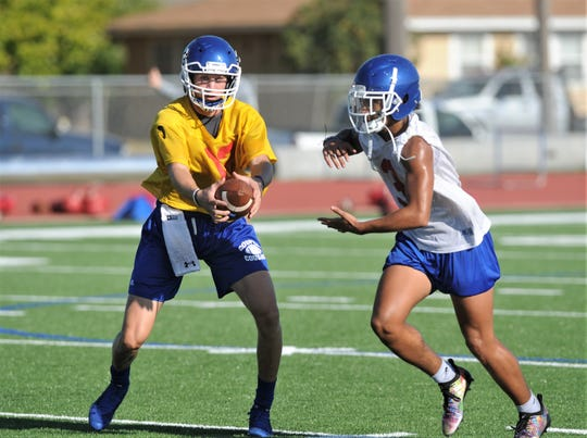Cooper quarterback Aidan Thompson, left, prepares to hand the ball off to running back Noah Garcia during the Cougars' first fall practice Monday, Aug. 12, 2019, at Cooper High School.
