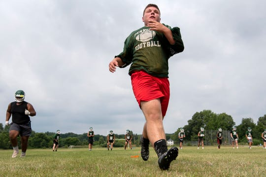 Early Monday morning, Pennfield High School football players attend their first practice of the season on Aug. 12, 2019 at Pennfield High School in Battle Creek, Mich.