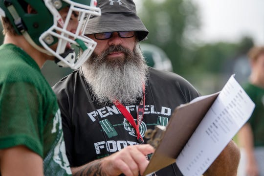 Pennfield head coach Mike Clothier works with his team during their first practice of the season on Aug. 12, 2019 at Pennfield High School in Battle Creek, Mich.