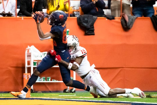 Syracuse receiver Taj Harris (left), a Palmyra graduate, drags North Carolina State's Chris Ingram during a touchdown reception last season.