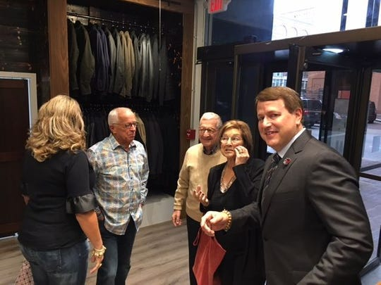 Chuck Hellman, right, owner of Hellman Clothiers, with famous Reds announcer Marty Brennaman, center, at the grand opening of the upscale men's store in the Carew Tower arcade.