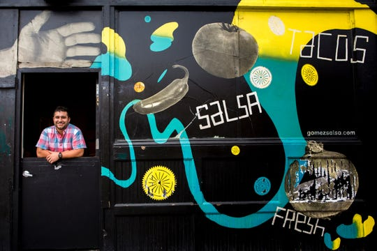 Andrew Gomez, owner of Gomez Salsa, poses in the walk-up/take-out window at Gomez Salsa on 12th Street in Over-the-Rhine on Aug. 9, 2016.