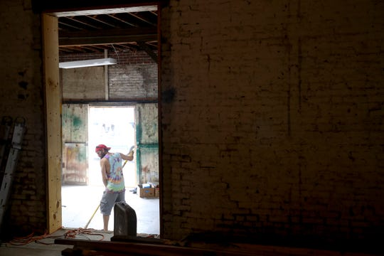A worker sweeps up a portion of a side hallway while building components for the new home of Manna Cafe Ministries at the future site of Manna Village in Clarksville, Tenn., on Monday, Aug. 12, 2019.