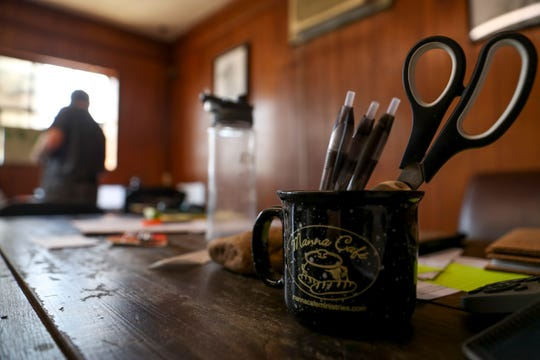 Pens and a pair of scissors stick out of a mug in the offices of Manna Cafe Ministries at the future site of Manna Village in Clarksville, Tenn., on Monday, Aug. 12, 2019.