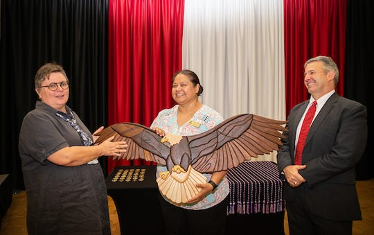 Dr. Beatrix Brockman presents an eagle she crafted to Jasmin Linares and retired Brig. Gen. Scott Brower.