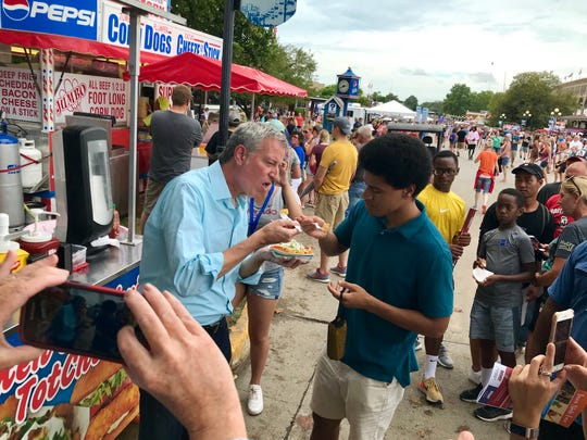 Mayor Bill de Blasio and his son, Dante, share an order of vegetarian tot-chos Sunday at the Iowa State Fair.