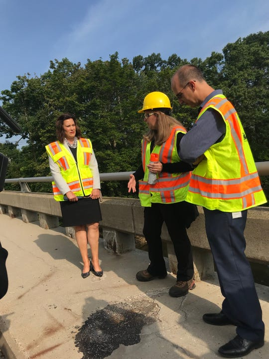 Gov. Gretchen Whitmer (left), MDOT official Rebecca Curtis, and Lansing Mayor Andy Schor inspect a deteriorating bridge in Lansing on Monday.