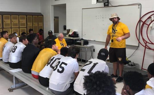 North Farmington coach Jon Herstein meets with his team as former Farmington Hills Harrison coach John Herrington listens before practice on Monday, Aug. 12, 2019.
