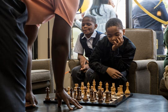 From left, Stephen Roberson, 12 looks on as his brother Shannon Roberson, 13 plays a game of chess during the grand opening of Shears & Shaves Barber and Spa on the Ave of Fashion in Detroit, Mich., Monday, Aug 12, 2019.