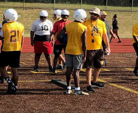 North Farmington coach John Herstein works with his lineman during practice on Monday, Aug. 12, 2019.