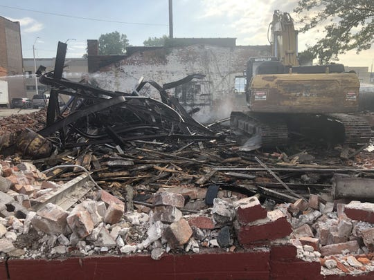 The former Gold Dollar bar was being demolished Monday after a mysterious fire in Julyravaged the vacant buildingowned by an entity linked to the billionaire owners of Little Caesars and the Detroit Tigers.