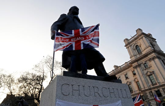 """In this March 29 photo a pro-Brexit demonstrator holds a British flag with the words """"Leave Means Leave"""" in front of the Winston Churchill statue in London."""