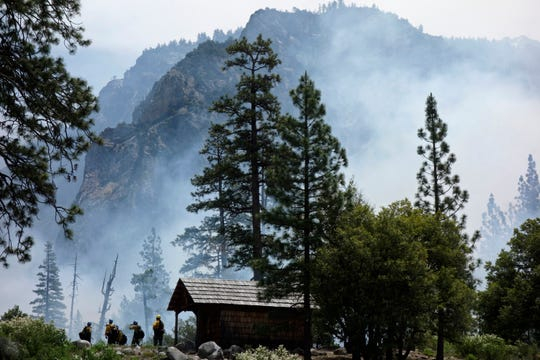 In this  June 11, 2019 photo, firefighters prepare to protect Knapp's Cabin, a storage shed from the 1920s that is the oldest building in Cedar Grove, during a prescribed burn at Kings Canyon National Park, Calif.