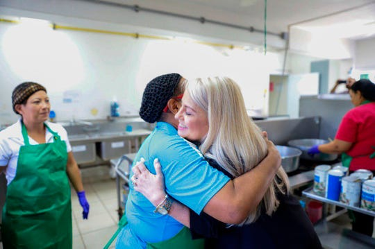 In this handout photo provided by the Governor's Office, Puerto Rico Gov. Wanda Vazquez embraces a cafeteria worker during a visit to the Ramon Marin Sola School, in Guaynabo, Puerto Rico, Monday, Aug. 12, 2019.