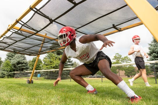 Players go through drills during the first day of high school football practice at Orchard Lake St. Mary's.