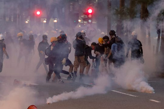 Protesters use traffic cones to cover the tear gas canisters fired by riot policemen during the anti-extradition bill protest in Hong Kong, Sunday. Police fired tear gas late Sunday afternoon to try to disperse a demonstration in Hong Kong as protesters took over streets in two parts of the Asian financial capital.