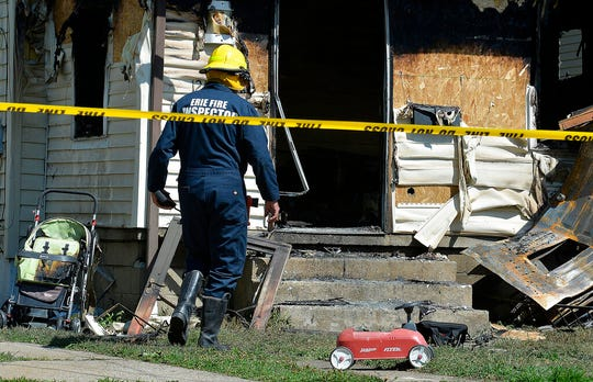 Erie Bureau of Fire Inspector Mark Polanski helps investigate a fatal fire at 1248 West 11th St. in Erie, Pa, on Sunday, Aug. 11, 2019. Three of five kids killed in a fire at a home child care center in Pennsylvania were the children of a volunteer firefighter who was responding to another call, an official said Monday.