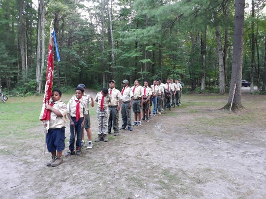 Members of Detroit's Boy Scout Troop 647, based at Hartford Memorial Baptist Church, in procession during a campout Aug. 3, 2019, at Cole Canoe Base Camp in Alger.