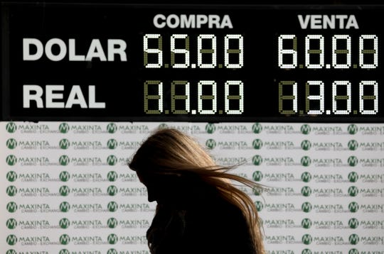 A woman walks past a currency exchange board in Buenos Aires, Argentina, Monday, Aug. 12, 2019.