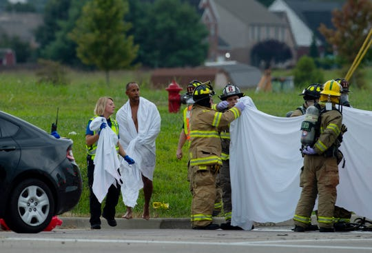 Emergency personnel lead Trooper Seth Rainey, second left, to a waiting ambulance as they continue their decontamination duties at the intersection of Indiana 66 and Grimm Road after a hazardous chemical spill Monday morning. A tractor-trailer's load spilled from its container while driving down the highway and landed on at least three vehicles. The chemical, Nitriles Liquid Toxic (Polyamide Oligomers), isn't life-threatening in this instance according to the official press release, but the exposure forced the decontamination of four people – including Trooper Rainey – on the side of the road where they were later transported to St. Vincent Hospital.
