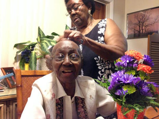 Regina Smith's daughter, Snoozie, styling her mother's hair before her 100th birthday celebration.