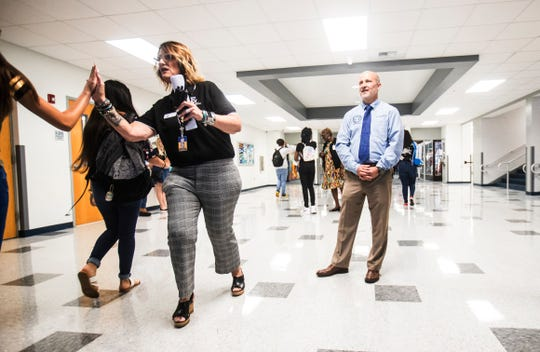 """Melissa Robery, left, the principal of East Lee High School in Lehigh Acres and Greg Adkins, the superintendent for Lee County Schools, greet students on the first day of school on Monday. The school increased its grade from a """"D"""" to """"C"""" on the state report card."""