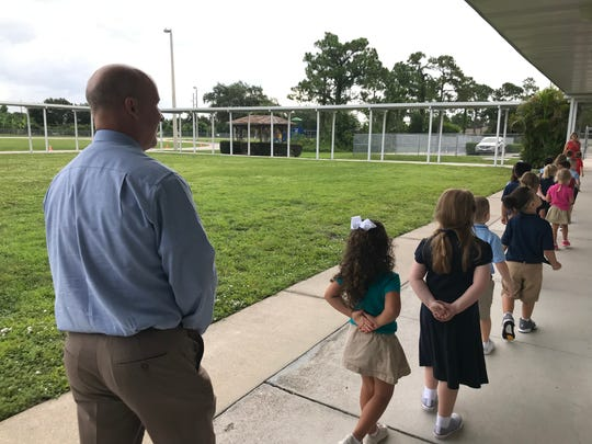 Lee County schools superintendent Greg Adkins walks in line behind a class of kindergarten students at Trafalgar Elementary School on the first day of class, Monday.