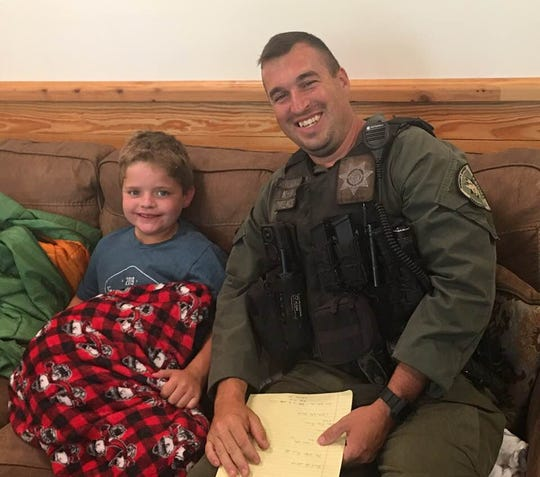 Matthew Yarbrough, 9, sits with Deputy Matthew Lovelace after being found in the wilderness outside YMCA Camp Greenville. Matthew had been missing overnight.