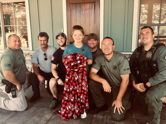 Matthew Yarbrough, 9, stands with deputies from the Greenville County Sheriff's Office after staff from the Green River Preserve found him Friday.  Matthew had gone missing from YMCA Camp Greenville Thursday.