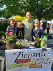 Zionsville Cultural District Directors Mamata Patel (left), Susan Schube, Mark Zelonis and Donna Monday gave away about 50 dahlia tubers earlier this year to promote the town's history with the beautiful flower.