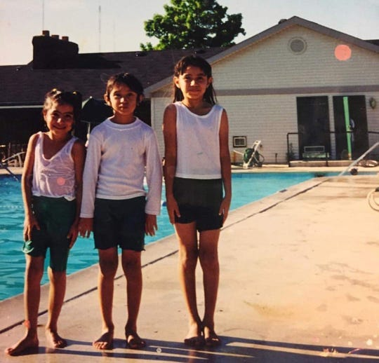 Karla Lopez-Owens (middle) poses with her sisters at an apartment complex in Indiana. They didn't have enough money for swimsuits so Owens' mother would cut pants into shorts for them to swim in.