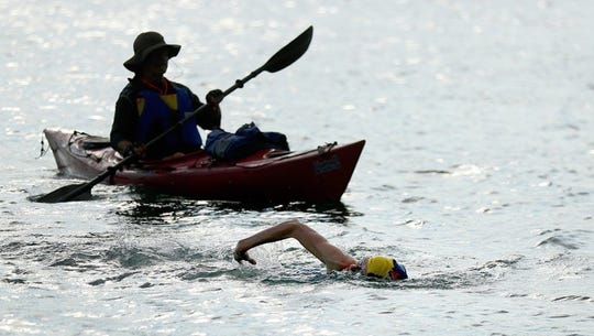 A woman swims across Cayuga Lake as a boater travels by to make sure swimmers are safe.