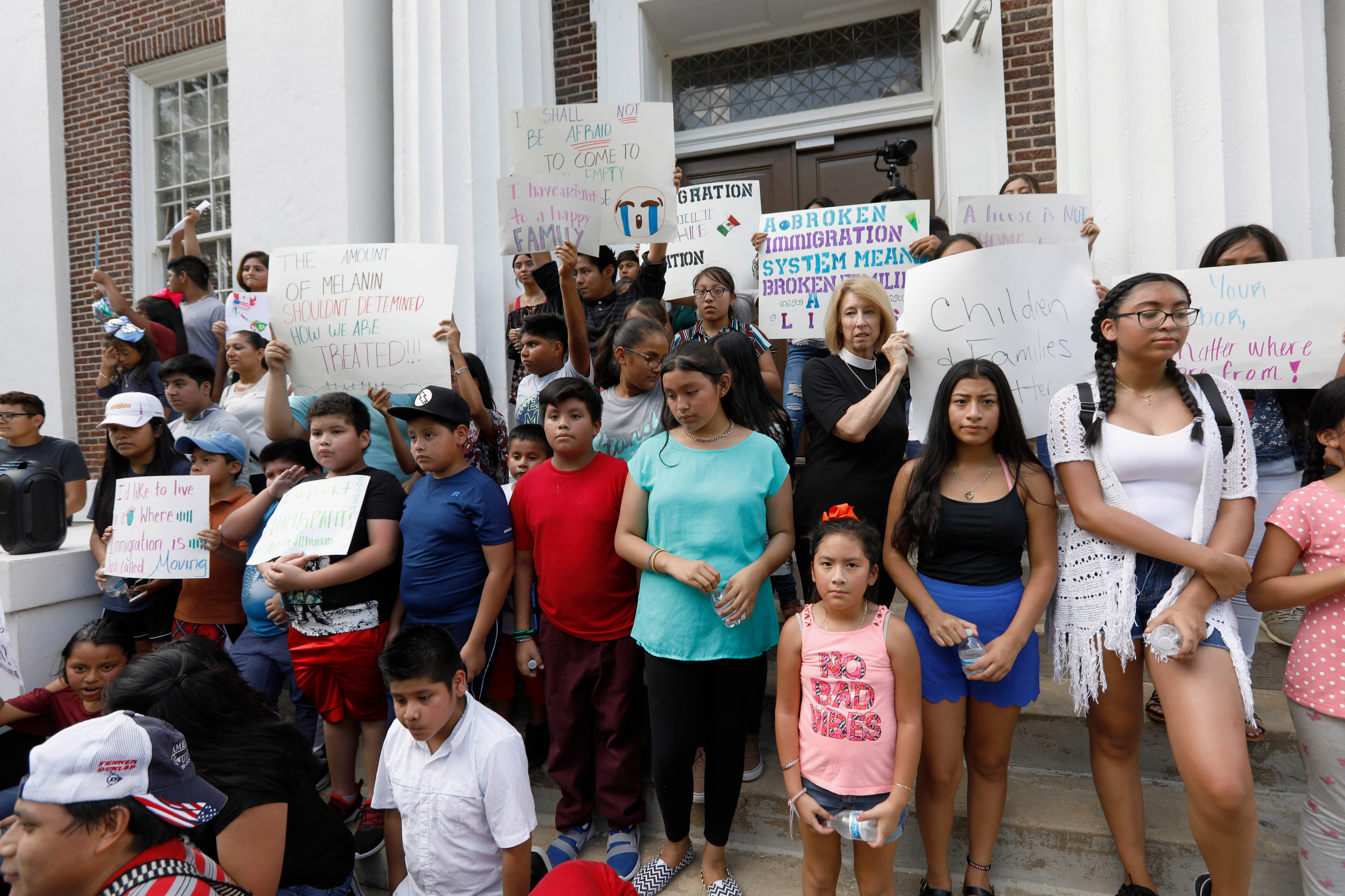 Children of mainly Latino immigrant parents hold signs in support of them and those individuals picked up during an immigration raid at chicken processing plants at the Madison County Courthouse in Canton, Miss., on Aug. 11, 2019.