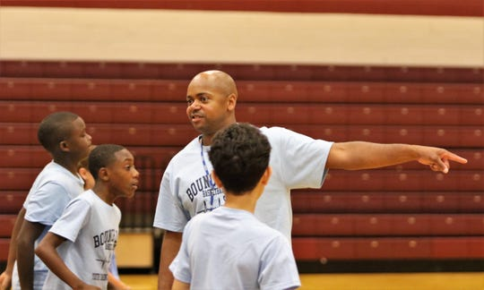 Dexter Williams directs players where to go on the court during drills at the Bounce Back Basketball Camp at Liberty Tech High School.