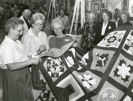 Lucille Kelly of Union County, Reva Weaver of Anderson County and Louise Kerr of Blount County check out the stitching on a quilt entry at the 1983 Tennessee Valley Fair.