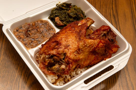 One of Laura's II's most popular orders is turkey wings stuffed with a crimson paste of minced garlic and spices served over rice with greens and beans on the side.