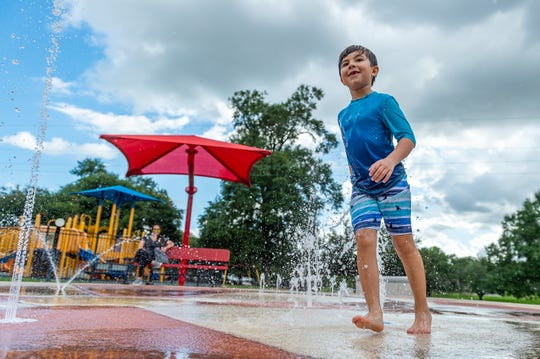 Seven-year-old Madden Cashat cools off at the splash pad at Girard Park as his mother Michelle Champagne watches from a bench.