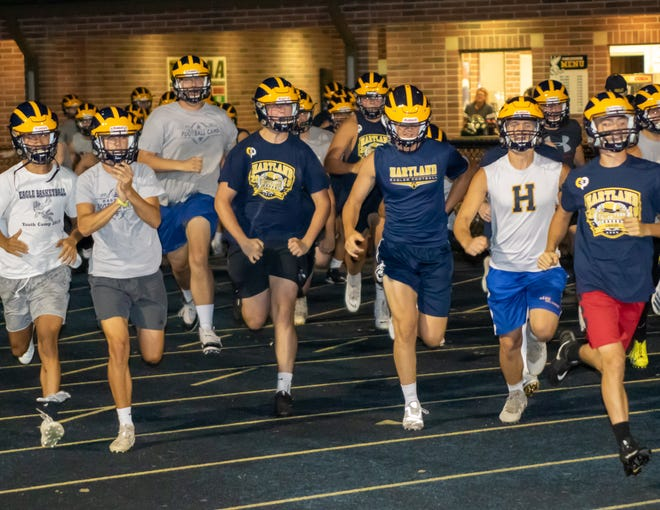 Hartland's football players run onto the field at midnight on Monday, Aug. 12, 2019 for the first practice of the season.