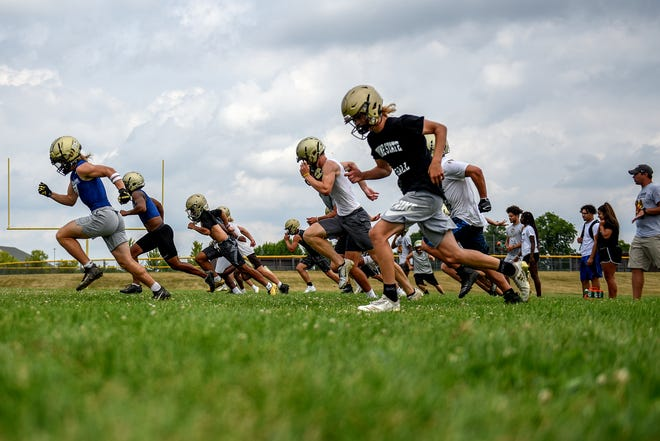 Members of Holt football team run sprints during the Rams opening day of football practice on Monday, Aug. 12, 2019, at Holt High School.