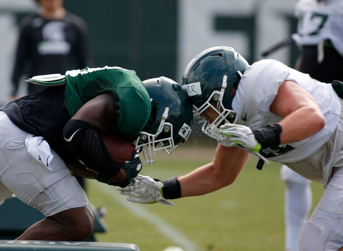 Michigan State running back Alante Thomas, left, and linebacker Ed Warinner collide as they run a drill during an NCAA college football practice, Monday, Aug. 12, 2019, in East Lansing, Mich.