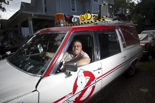 Lansing resident Aaron Aikman sits in his Ecto-1 replica vehicle, a 1984 Cadillac hearse.