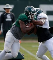 Michigan State running back La'Darius Jefferson, left, and linebacker Tyriq Thompson run a drill during an NCAA college football practice, Monday, Aug. 12, 2019, in East Lansing, Mich.