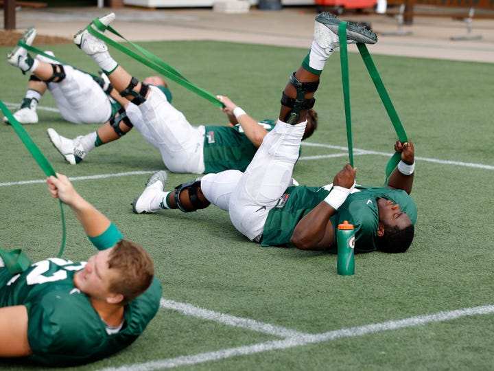 Michigan State offensive linemen Devonte Dobbs, right, and Luke Campbell, left, stretch during an NCAA college football practice, Monday, Aug. 12, 2019, in East Lansing, Mich.