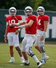 Michigan State quarterback Theo Day, center, throws a pass as Brian Lewerke, right, and Payton Thorne, left, watch during an NCAA college football practice, Monday, Aug. 12, 2019, in East Lansing, Mich.