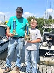 Biggest fish of the day trophy went to Little Brother Mark (right) on the Whitecap boat with Capt. Leon LeClair. Capt. LeClair (left) won the trophy for the largest overall catch of the day.