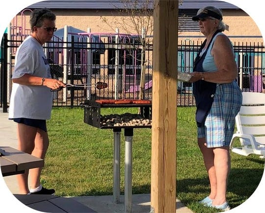 From left, Teresa Lupton and Sandy Stout of Mansfield Civitan Club grill hot dogs at a year-end party for the Unstoppables Baseball Team at the Mansfield YMCA.