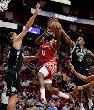 Rockets guard James Harden puts up a shot between Bucks center Brook Lopez and guard Eric Bledsoe during a game in Houston last season.